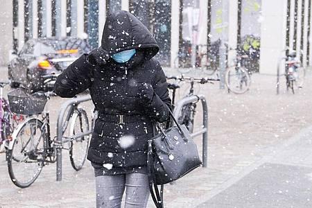 Eine Frau schützt sich mit Kapuze vor dem Schneeschauer in Berlin. Foto: Annette Riedl/dpa