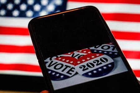 Die US-Wahl auf einem Smartphone-Bildschirm. Foto: Herwin Bahar/ZUMA Wire/dpa