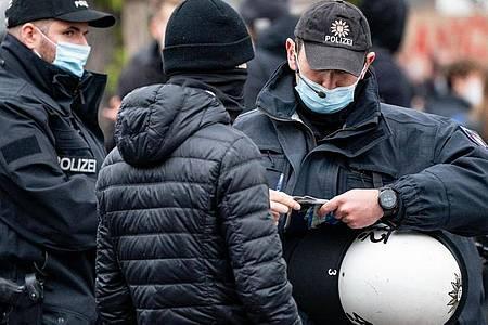 Polizisten kontrollieren die Personalien von einem Teilnehmer einer Demonstration in Hamburg. Foto: Axel Heimken/dpa