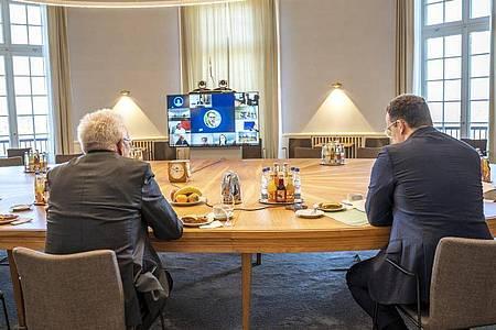 Gesundheitsminister Jens Spahn (r) und Baden-Württembergs Ministerpräsident Winfried Kretschmann bei einer Videokonferenz im Staatsministerium in Stuttgart. Foto: Jana Hoeffner/Staatsministerium Stuttgart/dpa