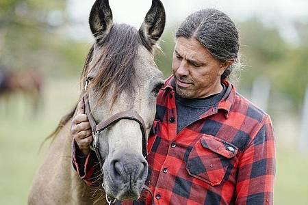 Dominic Sohl, Pächter eines Pferdehofes im Raum Heidelberg, steht mit einem Pferd auf einer Weide. Foto: Uwe Anspach/dpa