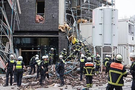Einsatzkräfte sichern das eingestürzte Gerüst an der Baustelle. Foto: Daniel Bockwoldt/dpa
