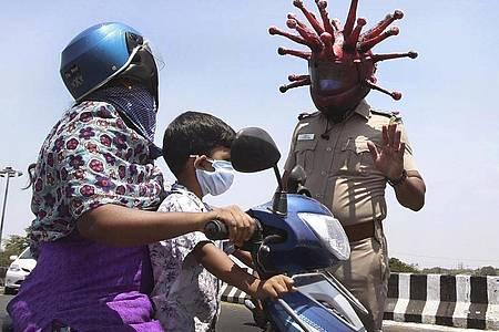 Ein Polizeibeamter im indischen Chennai trägt einen Helm, der einem Virus ähnelt, und weist Pendler auf die Einhaltung der Ausgangsbeschränkungen hin. Foto: R. Parthibhan/STR/AP/dpa