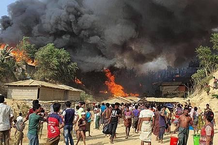 Zahlreiche Menschen betrachten den Rauch, der über dem in Flammen stehenden Lager aufsteigt. Foto: Shafiqur Rahman/AP/dpa