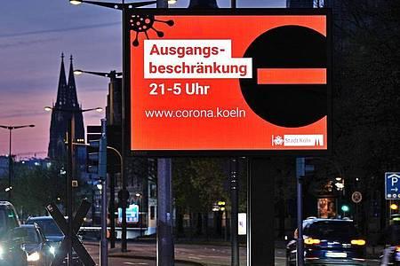 Auf einer Anzeigetafel in Köln wird auf die Ausgangsbeschränkung hingewiesen. Foto: Oliver Berg/dpa