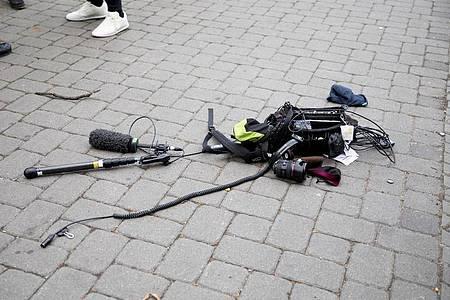 Die Ausrüstung des Kamerateams liegt nach der Attacke auf dem Boden. Foto: Christoph Soeder/dpa