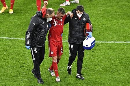Bayerns Joshua Kimmich geht nach einer ärztlichen Behandlung gestützt von den Betreuern vom Platz. Foto: Martin Meissner/Pool AP/dpa