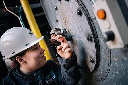 Durch ein kleines Bullauge prüft die angehende AnlagenmechanikerinLisa-Maria Schippl, ob der Verbrennungsvorgang im Kessel optimal läuft. Foto: Zacharie Scheurer/dpa-tmn