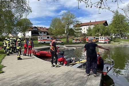 Einsatzkräfte stehen an dem Badesee bei Sulzberg im Oberallgäu. Foto: Davor Knappmeyer/-/dpa