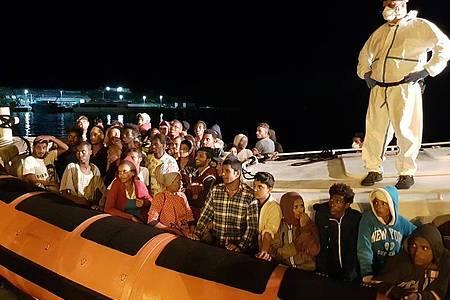 Flüchtlinge bereiten sich darauf vor, bei ihrer Ankunft im Hafen von Lampedusa aus einem Beiboot zu steigen. Foto: Elio Desiderio/ANSA/dpa