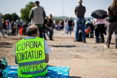 Ein Teilnehmer trägt auf dem Cannstatter Wasen bei der Protestkundgebung der Initiative «Querdenken 711» eine Warnweste mit der Aufschrift «Corona Diktatur stoppen». Foto: Christoph Schmidt/dpa