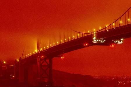 Die Golden Gate Bridge ist in orangefarbenem Licht durch die anhaltenden Waldbrände zu sehen. Foto: Frederic Larson/AP/dpa