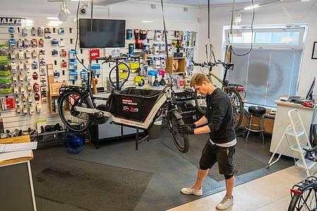 Geht es um Cargo- oder Mountainbikes wird ein Elektroantrieb auch für Jüngere interessant. Stefan Borschert kontrolliert das Vorderrad eines Lastenrads. Foto: Nicolas Armer/dpa-tmn