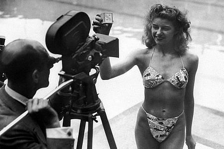 Micheline Bernardini, eine Nackttänzerin des Pariser Casinos, präsentiert am 5. Juli 1946 in einem Schwimmbad in Paris den ersten Bikini, den der französische Ingenieur Louis Reard entwickelt hatte. Zunächst erhielt das als schamlos empfundene Kleidungsstück vielerorts Badeverbot. Foto: -/AFP/dpa