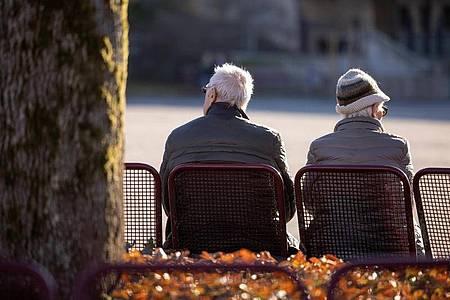 Ein Mann und eine Frau sitzen in der Innenstadt auf einer Bank im thüringischen Suhl. Foto: Michael Reichel/dpa-Zentralbild/dpa