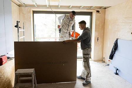 Jonas Schwarzwälder (r) und sein Ausbilder Egon Karl (l) arbeiten auf der Baustelle Hand in Hand. Foto: Philipp von Ditfurth/dpa-tmn