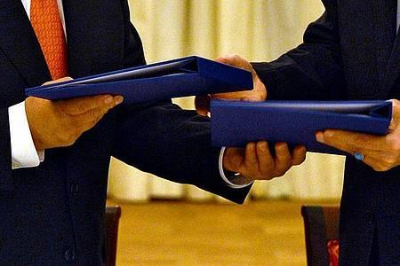 Der damalige Generaldirektor Yukiya Amano (l) und der Vize-Präsident der damalige Islmistischen Republik Iran Ali Akhbar Salehi (r) tauschen am 14.07.2015 in Wien die unterschriebenen Verträge, die das Iranische Atomprogramm regeln sollen. Foto: Dean Calma/IAEA/dpa