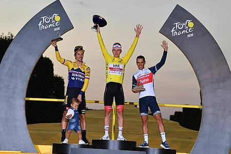 Der Zweitplatzierte Primoz Roglic (l-r) (mit seinem Sohn Lev), Tour-Sieger Tadej Pogacar und der Drittplatzierte Richie Porte feiern auf dem Podium. Foto: David Stockman/BELGA/dpa