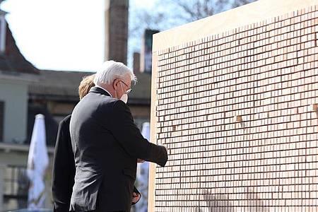 Bundespräsident Frank-Walter Steinmeier und seine Frau Elke Büdenbender vor der Installation «Verschwindende Wand - mit Botschaften, die bleiben». Foto: Ronny Hartmann/AFP-POOL/dpa