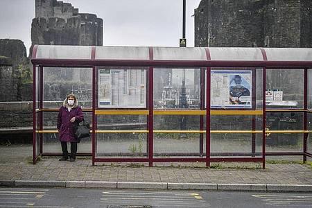 Eine Frau mit Mundschutz wartet in Caerphilly an einer Haltestelle auf den Bus. Medienberichtenn zufolge plant die Regierung inLondon einen erneutenlockdown vor. Foto: Ben Birchall/PA/AP/dpa