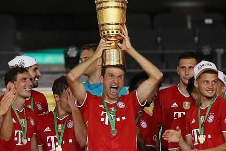 Münchens Thomas Müller hält die Trophäe nach dem Spiel hoch. Foto: Alexander Hassenstein/Getty Images Europe/Pool/dpa