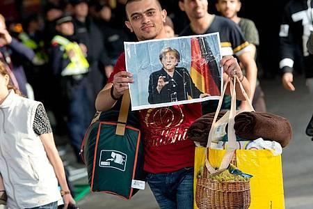 Ein Flüchtling, der kurz zuvor mit einem Zug angekommen ist, hält voller Hoffnung ein Foto von Angela Merkel in den Händen.(Archiv). Foto: Sven Hoppe/dpa