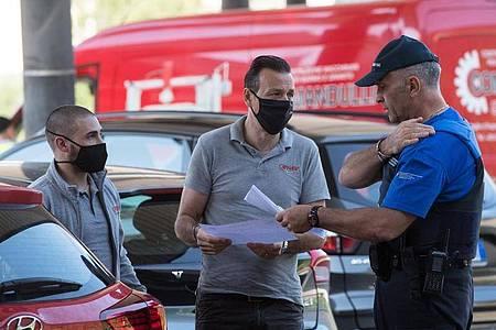 Zwei Männer sprechen am Grenzübergang mit einem Grenzbeamten und zeigen Dokumente vor. Foto: Alessandro Crinari/KEYSTONE/Ti-Press/dpa