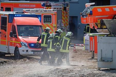Feuerwehrleute tragen ihre Ausrüstung zur Einsatzstelle auf die Baustelle. Foto: Henning Kaiser/dpa