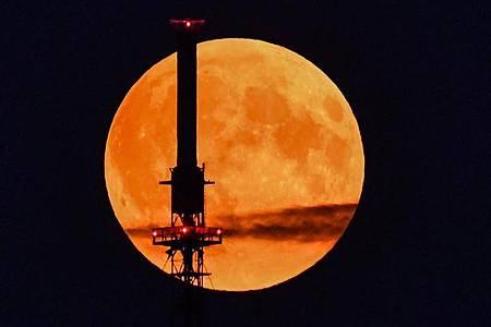 Der rötlich schimmernde Vollmond leuchtet hinter einem Funkmast. Foto: Patrick Pleul/dpa-Zentralbild/dpa