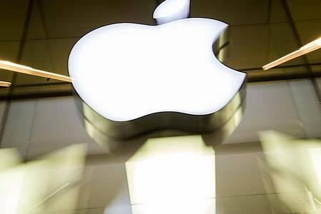 Das Apple-Logo an der Fassade eines Apple Stores. Foto: Peter Kneffel/dpa