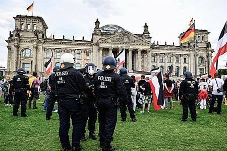 Teilnehmer einer Demonstration gegen die Corona-Maßnahmen stehen mit Reichsflaggen vor dem Reichstag. Foto: Fabian Sommer/dpa