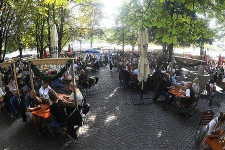 Gäste genießen in einem Biergarten auf dem Viktualienmarkt das schöne Wetter. Foto: Felix Hörhager/dpa