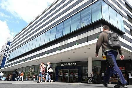 Passanten gehen auf der Frankfurter Einkaufsmeile Zeil am Eingang des Kaufhauses Karstadt vorbei. Foto: Arne Dedert/dpa