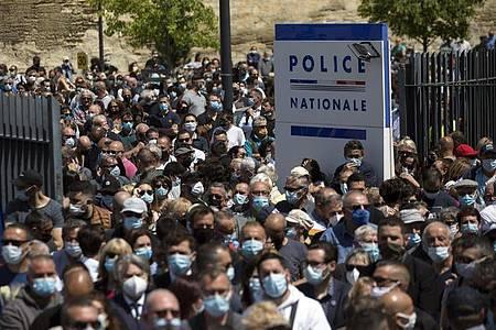Zahlreiche Polizeibeamte und Zivilisten versammeln sich an einer Polizeistation, um dem getöteten Polizisten zu gedenken. Foto: Daniel Cole/AP/dpa
