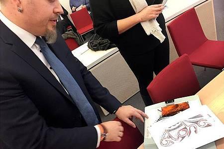 Polizeioberkommissar Jürgen Prichta hält bei der Verhandlung am Bayerischen Verwaltungsgerichthof die Entwürfe für sein geplantes Tattoo in den Händen. Foto: Britta Schultejans/dpa