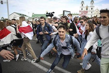 Belarussische Studenten rennen bei einer Kundgebung vor der Heilig-Geist-Kathedrale vor der Polizei weg. Foto: Uncredited/Tut.by/AP/dpa