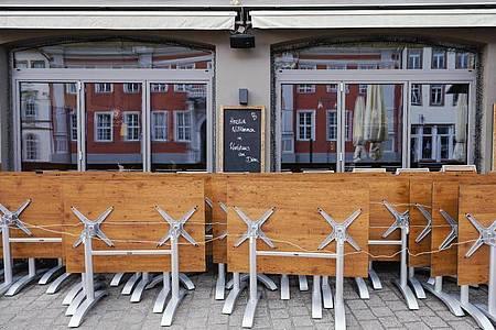 Hochgeklappte Tische stehen in der Fußgängerzone von Speyer vor einer Gastwirtschaft (Symbol). Foto: Uwe Anspach/dpa