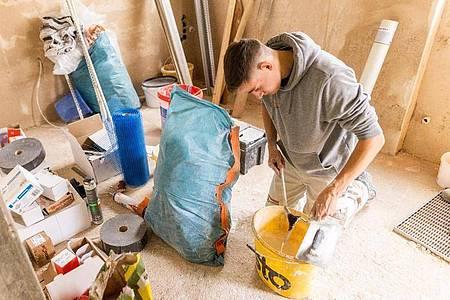 Gips, Mörtel, Farbe: Solche Materialien gehören zur Arbeitswelt von Jonas Schwarzwälder. Der angehende Stuckateur reinigt auf einer Baustelle sein Werkzeug. Foto: Philipp von Ditfurth/dpa-tmn