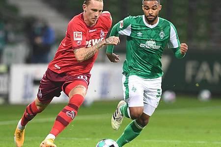 Kölns Marius Wolf (l) kämpft gegen Werders Jean-Manuel Mbom um den Ball. Foto: Carmen Jaspersen/dpa