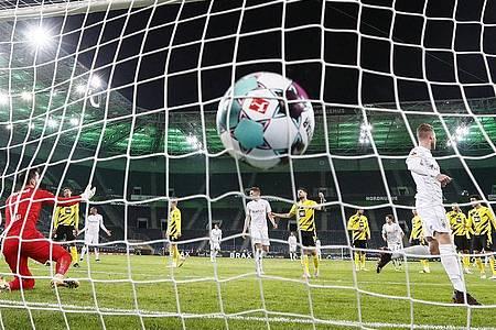 Mönchengladbachs Nico Elvedi (r) erzielt das zweite Tor gegen Dortmunds Torhüter Roman Bürki (l). Foto: Martin Meissner/Pool AP/dpa