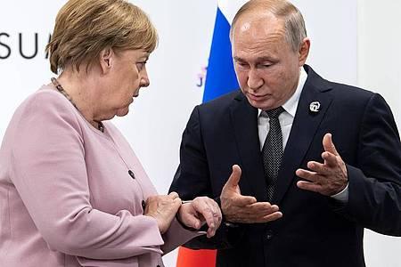 Bundeskanzlerin Angela Merkel spricht mit Kremlchef Wladimir Putin. Foto: Bernd von Jutrczenka/dpa/Archiv