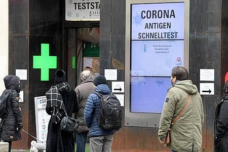 Menschen warten vor einer Apotheke in Wien auf einen Schnelltest. Die Sieben-Tage-Inzidenz liegt in Österreich bei rund 240. Foto: Roland Schlager/APA/dpa