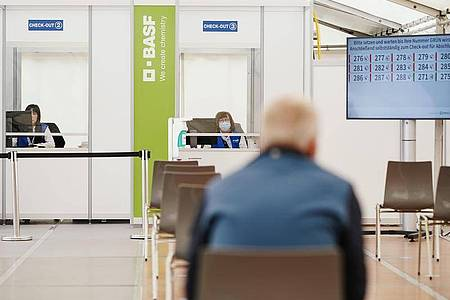 Ein geimpfter Mitarbeiter sitzt im BASF-Impfzentrum im Wartebereich, in dem mögliche Nebenwirkungen der Corona-Impfung beobachtet werden. Foto: Uwe Anspach/dpa