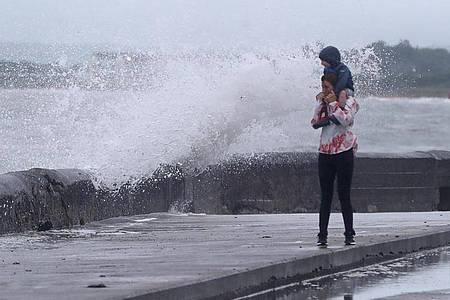 """Eine Welle tritt über das Ufer während eine Frau mit einem Kind auf den Schultern an der Strandpromenade geht. Sturmtief """"Ellen"""" trifft auf die Küste Irlands. Foto: Niall Carson/PA Wire/dpa"""