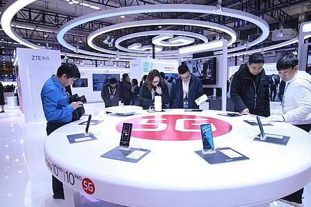 Besucher schauen in Peking neue Smartphones mit 5G-Technologie an. Foto: Chen Xiaogen/SIPA Asia via ZUMA Wire/dpa