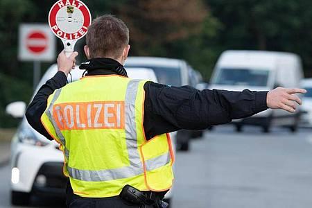 Ein Polizist steht im Rahmen eines Kontrolleinsatzes auf einem Autobahn-Parkplatz. Foto: Sebastian Kahnert/dpa-Zentralbild/dpa