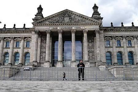 Polizeibeamte sichern hinter Absperrzäunen das Reichstagsgebäude. Foto: Kay Nietfeld/dpa
