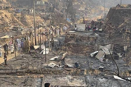 Rohingya-Geflüchtete betrachten nach dem Brand die Überreste des Flüchtlingslager. Foto: Shafiqur Rahman/AP/dpa