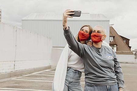 Zwei Frauen mit roten Masken machen ein Selfie von sich auf einem Hausdach
