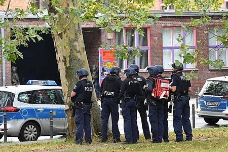Einsatzkräfte der Polizei stehen an einem Oberstufenzentrum in Rummelsburg. Foto: Paul Zinken/dpa-Zentralbild/dpa